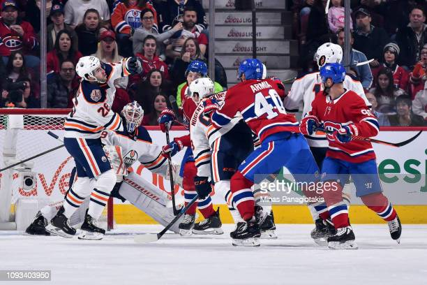 Brandon Manning of the Edmonton Oilers tries to hit the puck out of the air against the Montreal Canadiens during the NHL game at the Bell Centre on...