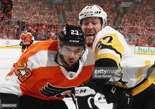 Brandon Manning of the Philadelphia Flyers and Carter Rowney of the Pittsburgh Penguins battle in the corner during the first period in Game Six of...