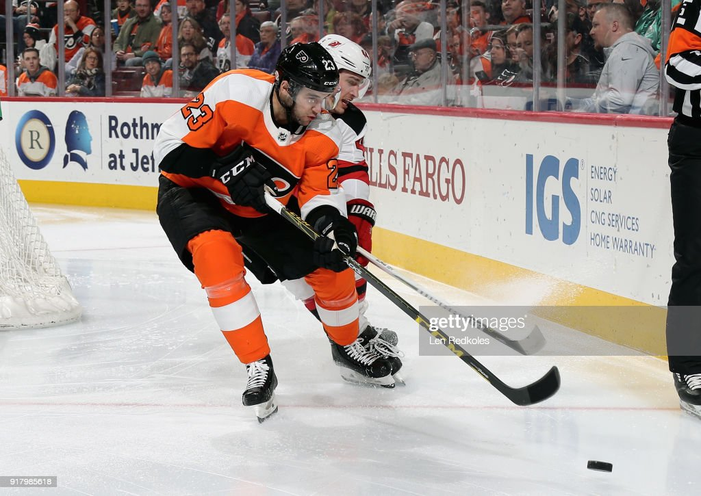 Brandon Manning #23 of the Philadelphia Flyers skates towards the loose puck while being pursued by Miles Wood #44 of the New Jersey Devils on February 13, 2018 at the Wells Fargo Center in Philadelphia, Pennsylvania. The Devils went on to defeat the Flyers 5-4 in a shootout.