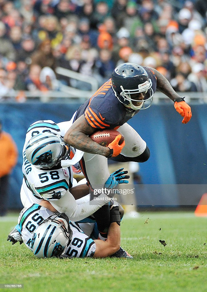 Brandon Marshall #15 of the Chicago Bears is tackled by Thomas Davis #58 of the Carolina Panthers and Luke Kuechly #59 on October 28, 2012 at Soldier Field in Chicago, Illinois.