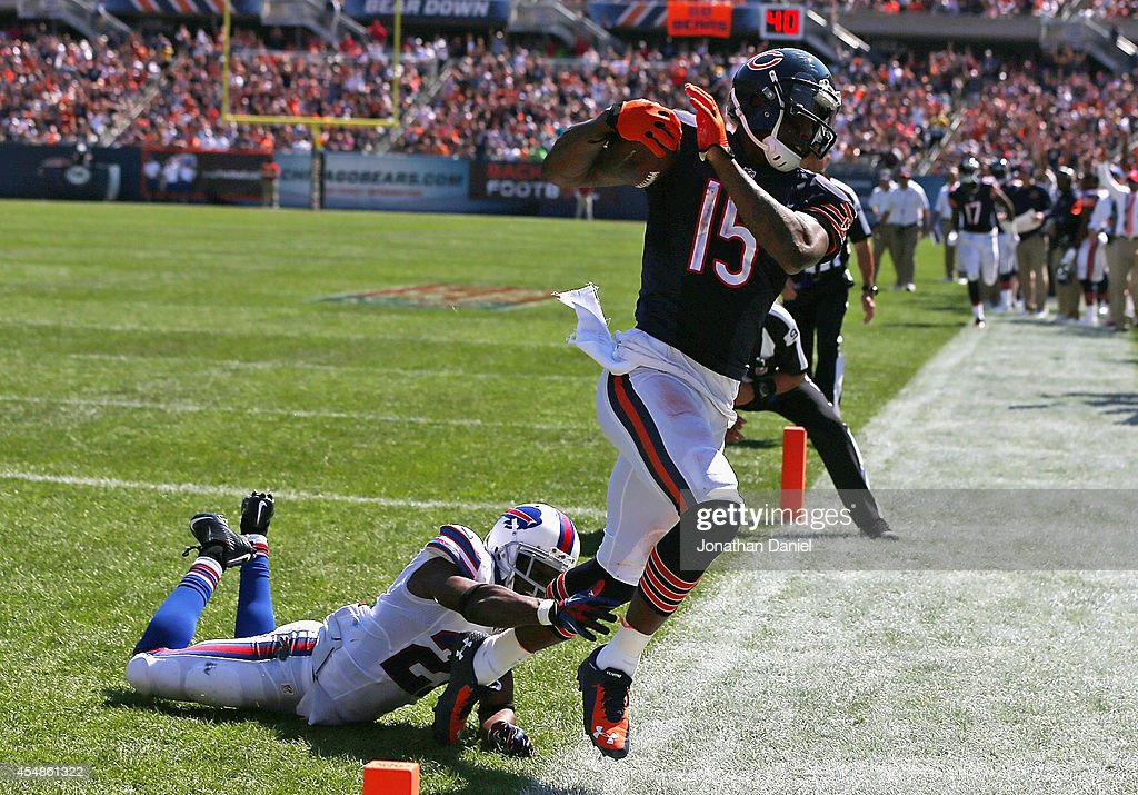 Brandon Marshall #15 of the Chicago Bears slips by Leodis McKelvin #21 of the Buffalo Bills to score a third quarter touchdown at Soldier Field on September 7, 2014 in Chicago, Illinois.