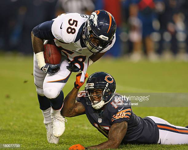 Brandon Marshall of the Chicago Bears tries to bring down Von Miller of the Denver Broncos after Miller intercepted a pass during a preseason game at...