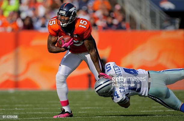 Brandon Marshall of the Denver Broncos makes a reception as Bobby Carpenter of the Dallas Cowboys makes the tackle during NFL action at Invesco Field...