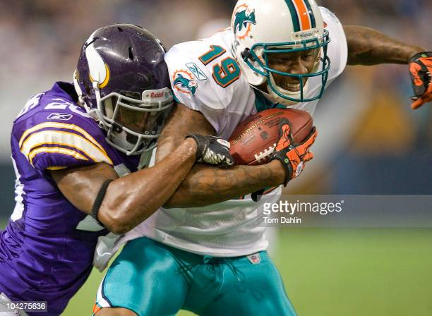 Brandon Marshall of the Miami Dolphins is tackled by Madieu Williams of the Minnesota Vikings during an NFL game at Mall of America Field at the...