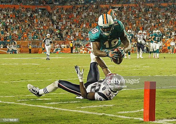 Brandon Marshall of the Miami Dolphins scores a touchdown over Devin McCourty of the New England Patriots during a game at Sun Life Stadium on...