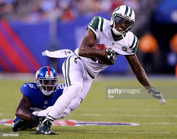 Brandon Marshall of the New York Jets carries the ball as Jeromy Miles of the New York Giants defends during preseason action at MetLife Stadium on...