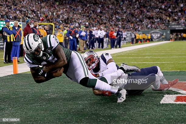 Brandon Marshall of the New York Jets catches a one yard touchdown pass against Malcolm Butler of the New England Patriots during the second quarter...