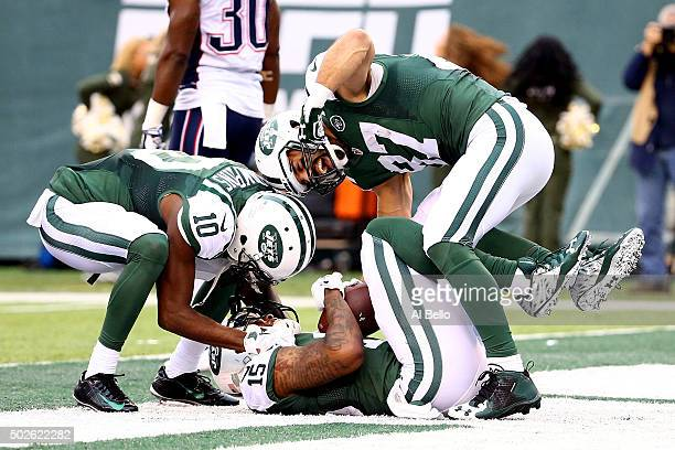 Brandon Marshall of the New York Jets celebrates with his teammates Kenbrell Thompkins and Eric Decker after scoring a 33 yard touchdown in the third...