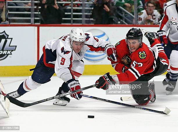 Brandon Mashinter of the Chicago Blackhawks falls to the ice as he gets off a shot under pressure from Dmitry Orlov of the Washington Capitals at the...
