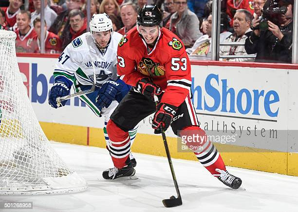 Brandon Mashinter of the Chicago Blackhawks grabs the puck as Sven Baertschi of the Vancouver Canucks follows during the NHL game at the United...