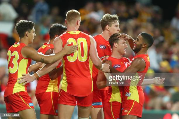 Brandon Matera of the Suns celebrates a goal with team mates during the round three AFL match between the Gold Coast Suns and the Hawthorn Hawks at...