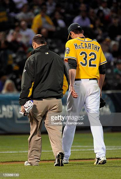 Brandon McCarthy of the Oakland Athletics walks off the field with trainer Nick Paparesta after he was hit in the knee with a linedrive off the bat...