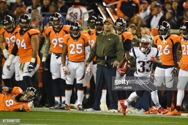 Brandon McManus of the Denver Broncos fails to tackle Dion Lewis of the New England Patriots on his way to the end zone on a kickoff in the first...