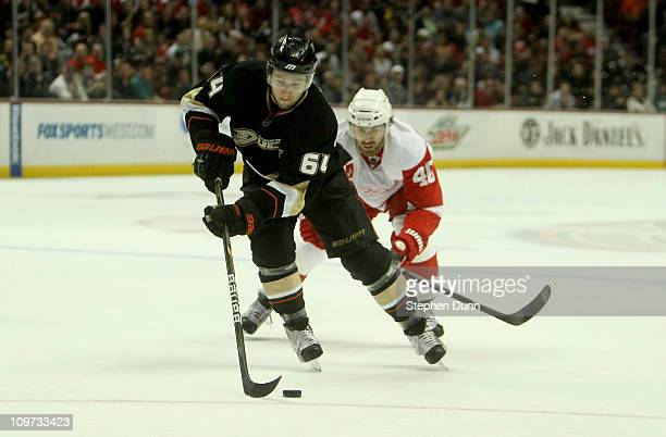 Brandon McMillan of the Anaheim Ducks cxarries the puck in front of Henrik Zetterberg of the Detroit Red Wings on March 2 2011 at the Honda Center in...