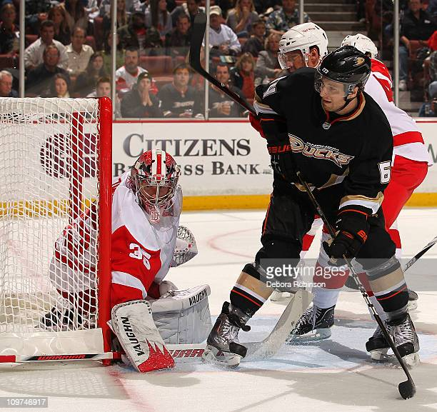 Brandon McMillan of the Anaheim Ducks defends outside the crease against Jimmy Howard of the Detroit Red Wings during the game on March 2 2011 at...