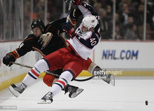 Brandon McMillan of the Anaheim Ducks is hit by Jared Boll of the Columbus Blue Jackets in the third period at the Honda Center on January 7, 2011 in...