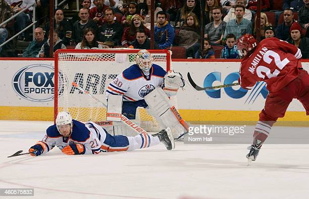 Brandon McMillan of the Arizona Coyotes shoots the puck toward goaltender Ben Scrivens of the Edmonton Oilers as Andrew Ference of the Oilers tries...