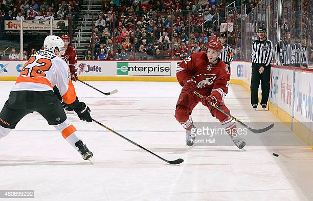 Brandon McMillan of the Arizona Coyotes skates with the puck as Luke Schenn of the Philadelphia Flyers defends during the second period at Gila River...