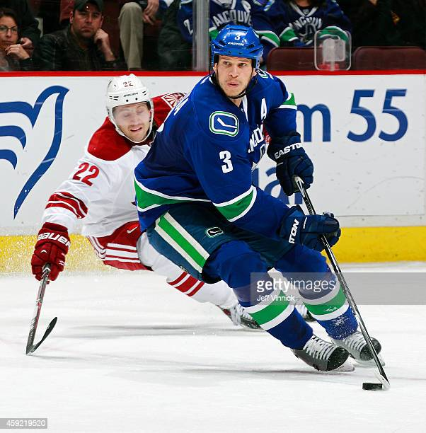Brandon McMillan of the Arizona Coyotes tries to check Kevin Bieksa of the Vancouver Canucks as he skates up ice with the puck during their NHL game...