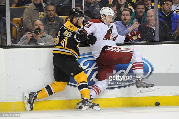 Brandon McMillan of the Phoenix Coyotes fights for the puck against David Krejci of the Boston Bruins at the TD Garden on March 13 2014 in Boston...