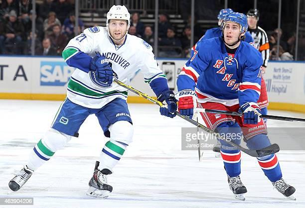 Brandon McMillan of the Vancouver Canucks skates against John Moore of the New York Rangers at Madison Square Garden on February 19 2015 in New York...