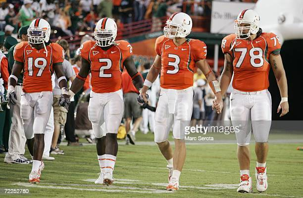 Brandon Meriweather, Jon Beason, Kyle Wright and Anthony Wollschlager of the Miami Hurricanes walk on the field against the Florida International...