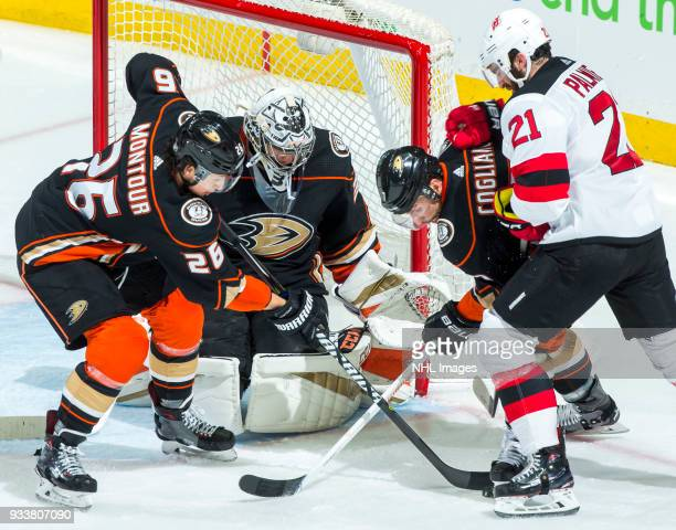 Brandon Montour and Andrew Cogliano of the Anaheim Ducks battle for the puck with Kyle Palmieri of the New Jersey Devils as goalie John Gibson of the...