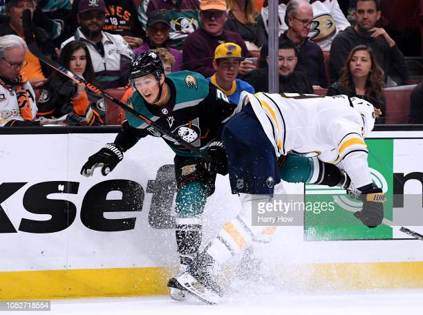 Brandon Montour of the Anaheim Ducks takes a hit along the boards from Jake McCabe of the Buffalo Sabres during the first period at Honda Center on...