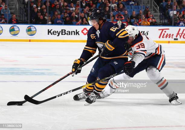 Brandon Montour of the Buffalo Sabres battles against Alex Chiasson of the Edmonton Oilers during an NHL game on March 4 2019 at KeyBank Center in...