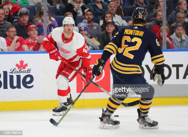Brandon Montour of the Buffalo Sabres looks to block a pass by Darren Helm of the Detroit Red Wings during the first period at KeyBank Center on...