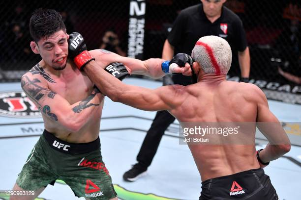 Brandon Moreno of Mexico and Deiveson Figueiredo of Brazil exchange punches in their flyweight championship bout during the UFC 256 event at UFC APEX...