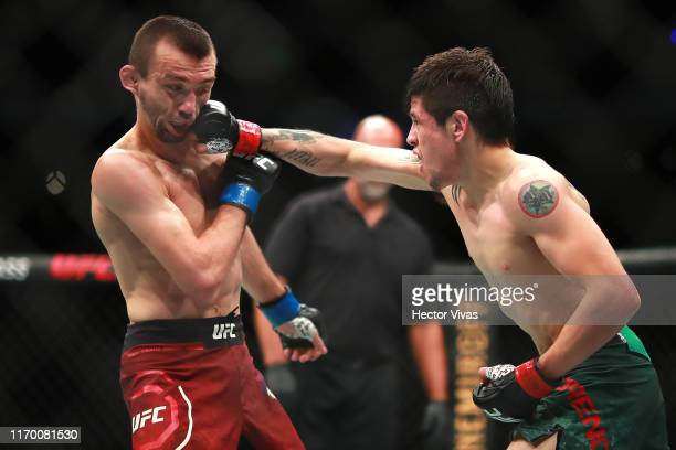 Brandon Moreno of Mexico punches Askar Askarov of Russia in their flyweight bout during UFC Fight Night event at Arena Ciudad de Mexico on September...