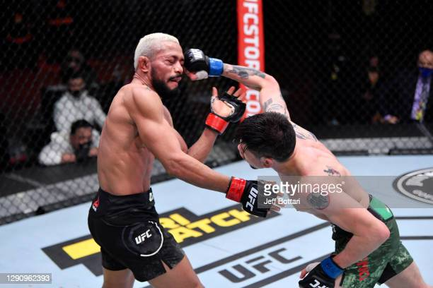 Brandon Moreno of Mexico punches Deiveson Figueiredo of Brazil in their flyweight championship bout during the UFC 256 event at UFC APEX on December...