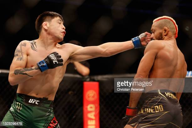 Brandon Moreno of Mexico throws a left on Deiveson Figueiredo of Brazil during their UFC 263 flyweight championship match at Gila River Arena on June...