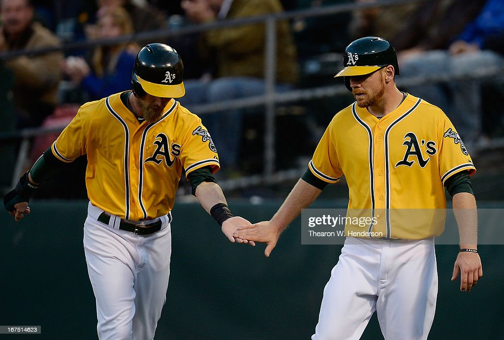 Brandon Moss (R) and Josh Reddick (L) of the Oakland Athletics celebrate after they both scored on a two-run double hit by Josh Donaldson (not pictured) against the Baltimore Orioles in the second inning at O.co Coliseum on April 25, 2013 in Oakland, California.