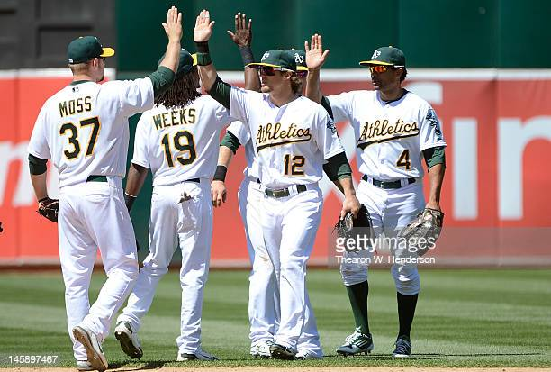 Brandon Moss Jemile Weeks Collin Cowgill and Coco Crisp celebrate defeating the Texas Rangers 7 to 1 at Oco Coliseum on June 7 2012 in Oakland...