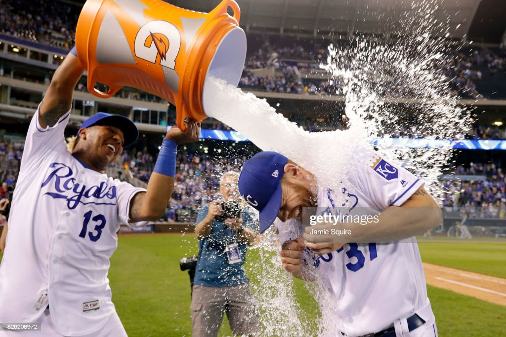 Brandon Moss #37 of the Kansas City Royals is doused with water by catcher Salvador Perez #13 as Kansas City Star photographer John Sleezer looks on after the Royals defeated the Seattle Mariners 6-4 to win the game at Kauffman Stadium on August 3, 2017 in Kansas City, Missouri.