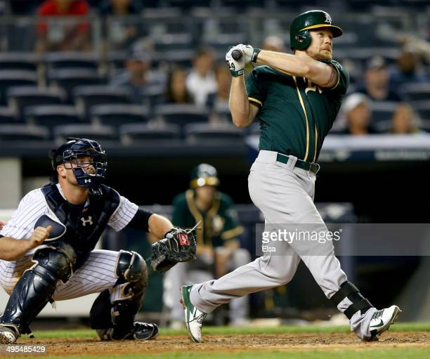 Brandon Moss of the Oakland Athletics hits a solo home run in the 10th inning as Brian McCann of the New York Yankees defends on June 3 2014 at...