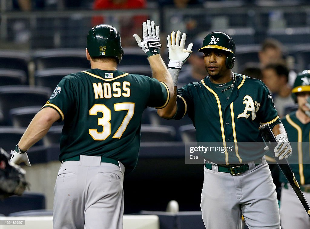 Brandon Moss #37 of the Oakland Athletics is congratulated by teammate Yoenis Cespedes #52 after Moss hit a solo home run in the 10th inning against the New York Yankees on June 3, 2014 at Yankee Stadium in the Bronx borough of New York City.