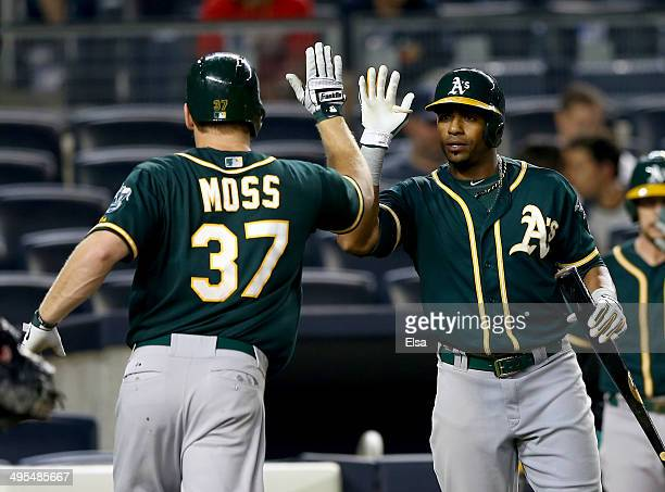 Brandon Moss of the Oakland Athletics is congratulated by teammate Yoenis Cespedes after Moss hit a solo home run in the 10th inning against the New...