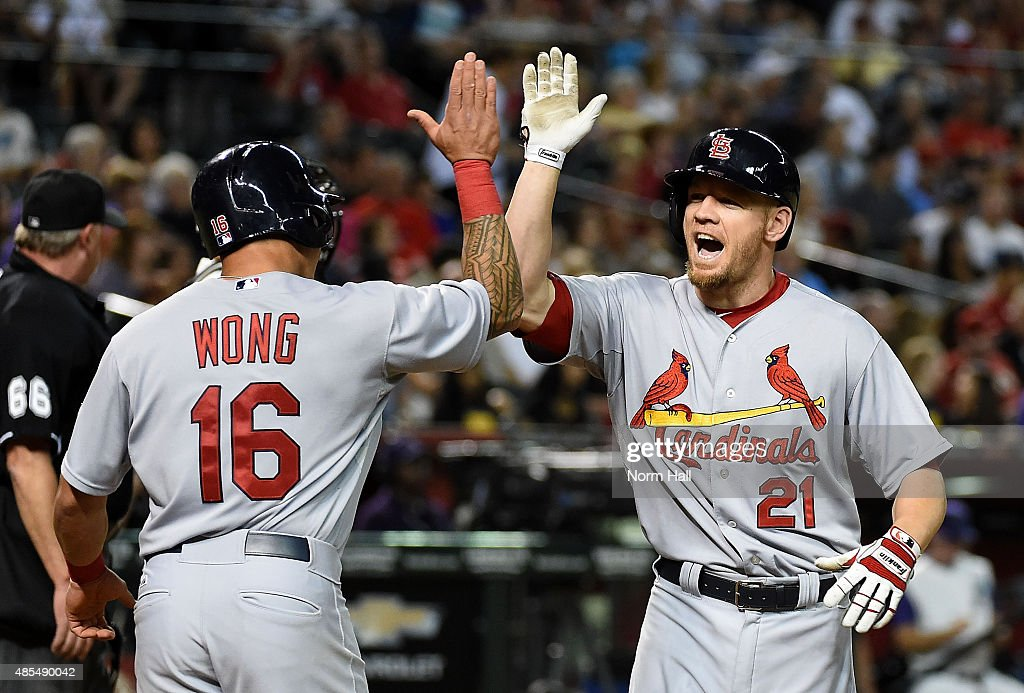 Brandon Moss #21 of the St Louis Cardinals celebrates with teammate Kolten Wong #16 after hitting a home run during the fifth inning against the Arizona Diamondbacks at Chase Field on August 27, 2015 in Phoenix, Arizona.