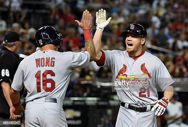 Brandon Moss of the St Louis Cardinals celebrates with teammate Kolten Wong after hitting a home run during the fifth inning against the Arizona...