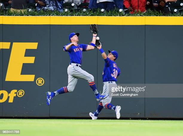 Brandon Nimmo and Michael Conforto of the New York Mets are unable to make the catch on a fly ball in the second inning against the Atlanta Braves at...