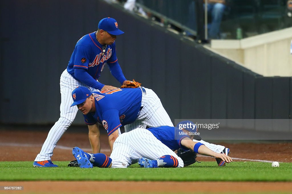 Brandon Nimmo #9, Jay Bruce #19 and Asdrubal Cabrera #13 of the New York Mets collide pursuing a double off the bat of Ian Desmond #20 of the Colorado Rockies in the first inning at Citi Field on May 4, 2018 in the Flushing neighborhood of the Queens borough of New York City.