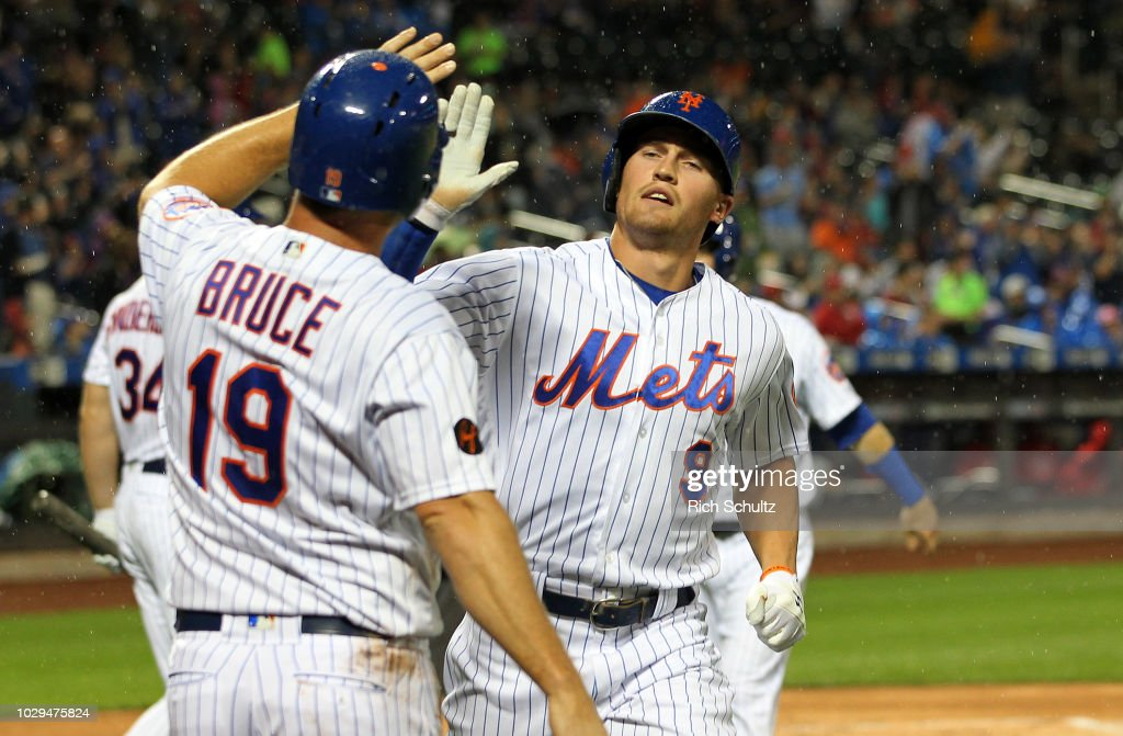 Brandon Nimmo #9 of the New York Mets high-fives Jay Bruce #19 after both scored along with Todd Frazier #21 on a three-run double by Tomas Nido #3 against the Philadelphia Phillies during the second inning at Citi Field on September 8, 2018 in the Flushing neighborhood of the Queens borough of New York City.