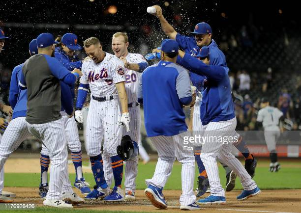 Brandon Nimmo of the New York Mets is congratulated by teammates as Pete Alonso pulls at his jersey after Nimmo scored the game winning run with a...