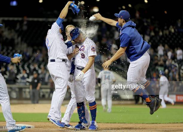 Brandon Nimmo of the New York Mets is congratulated by teammates Juan Lagares and Pete Alonso after Nimmo scored the game winning run with a bases...