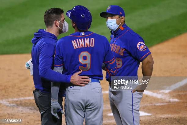 Brandon Nimmo of the New York Mets is looked on by a member of the Mets medical staff and manager Luis Rojas after injuring his hand while batting...