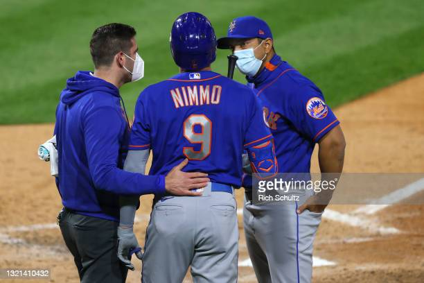 Brandon Nimmo of the New York Mets is looked on by trainer Brian Chicklo and manager Luis Rojas after injuring his hand while batting during the...