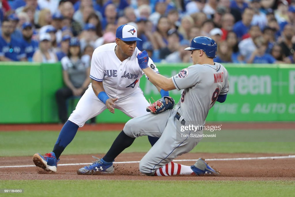 Brandon Nimmo #9 of the New York Mets is tagged out attempting to steal third base by Yangervis Solarte #26 of the Toronto Blue Jays in the fifth inning during MLB game action at Rogers Centre on July 3, 2018 in Toronto, Canada.